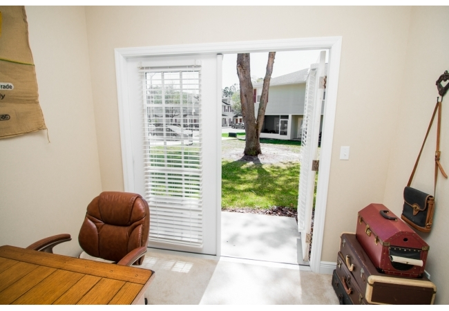 French doors lead to a back screened in porch, or a concrete slab depending on the unit.