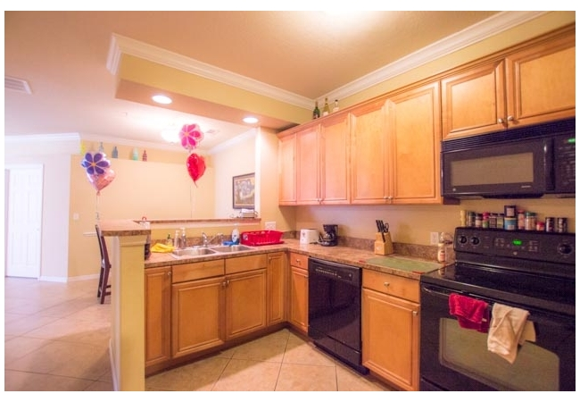 The open kitchen features crown molding, real wood cabinetry, and an elevated breakfast bar.
