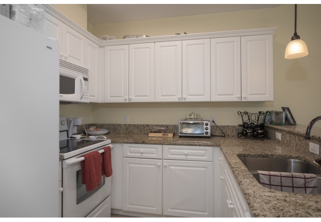 Condos have luxurious kitchens with white cabinetry and granite counter tops.