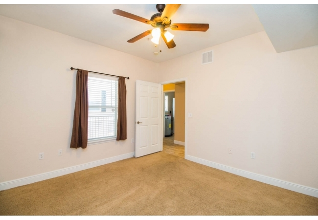 In the distance you can see the entry hall and door leading to a convenient laundry room.