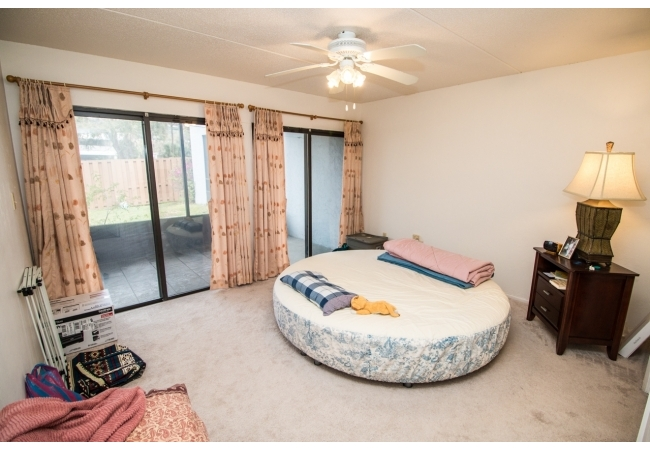 In addition to an interior door, the bedroom depicted is connected with the  living room via the screened porch..